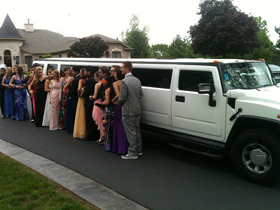 Group of kids outside of a Hummer limousine for prom