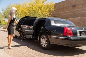 Limo Service Scottsdale stretch limo with woman holding back door open